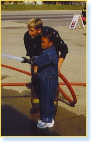 Firefighter helps child work hose
