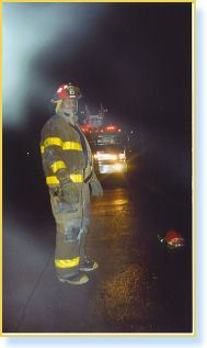 Firefighter stands on road